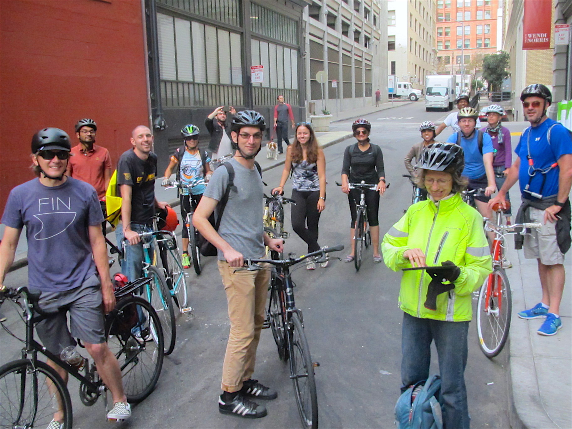 A group of smiling bicycle riders on an urban side street in San Francisco.