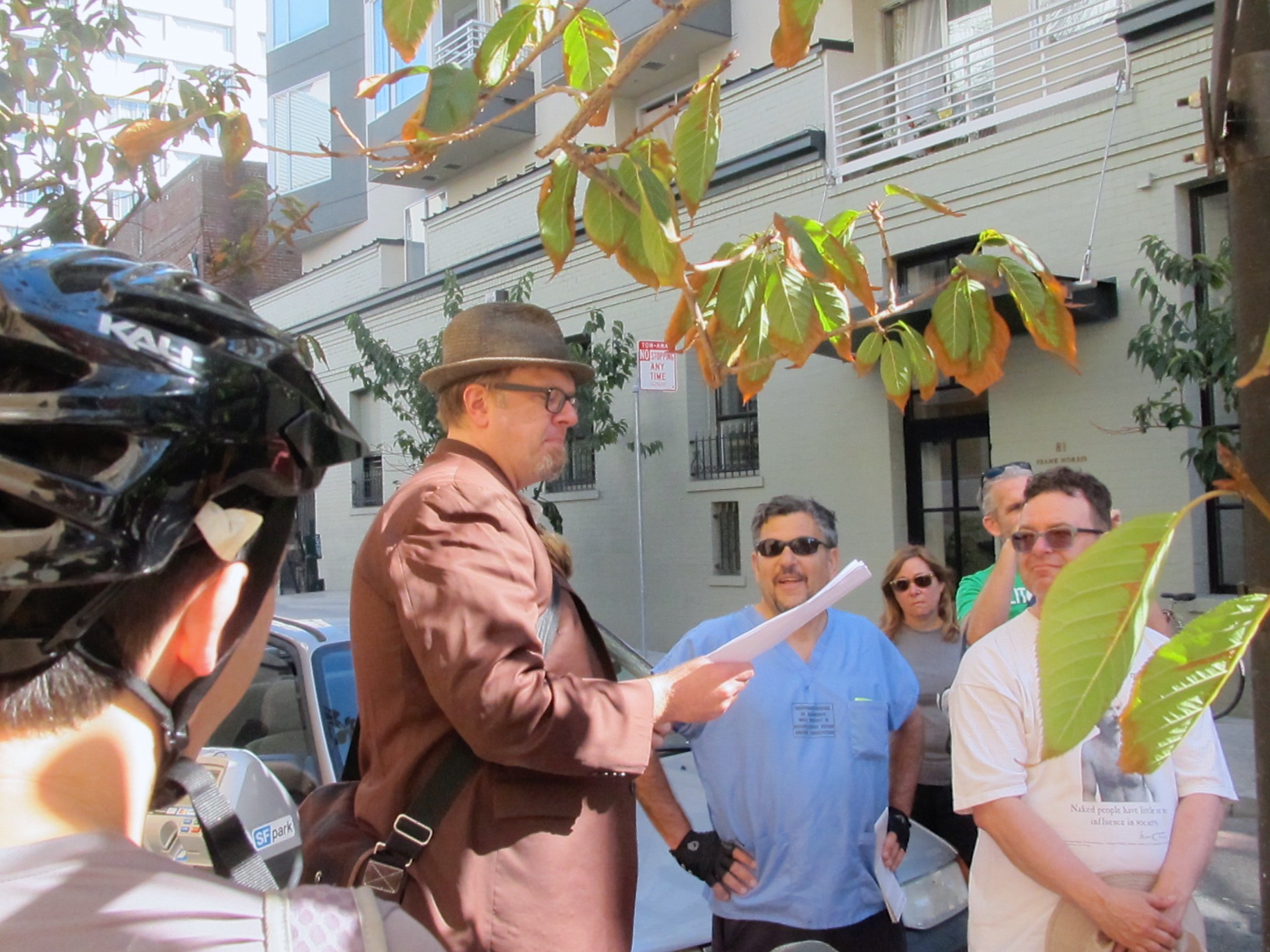 A reader, Jim Nelson, wearing a brown hat and suit jacket, reads to a group of bicycle riders on an urban side street in San Francisco.