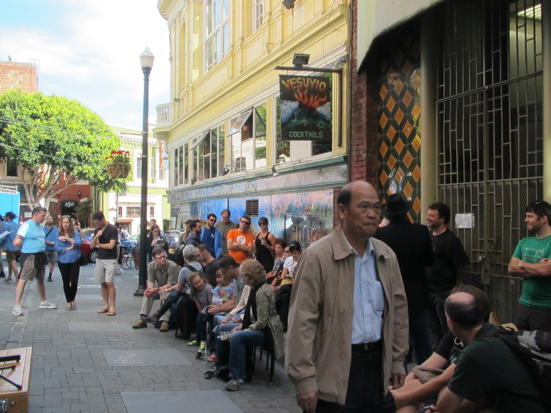 A gathering of people, some seated and some standing, on Jack Kerouac Alley outside of Vesuvio bar.