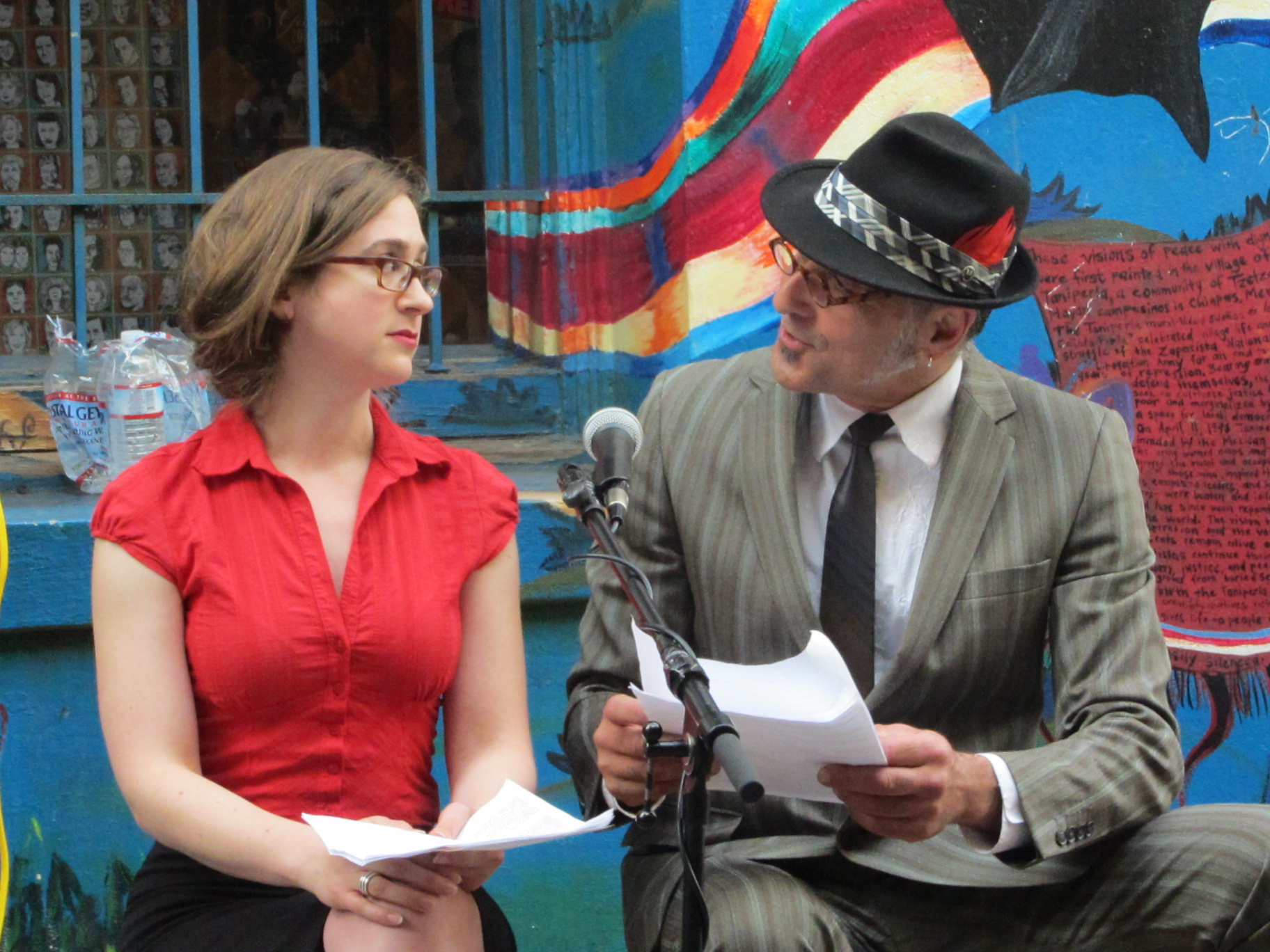 Two performers, Beck Hirshfeld, a young woman in a red button down shirt and glasses, Steffanos X, a middle-aged man in a grey striped suit and a nice fedora with a red feather, seated in front of a colorful mural.