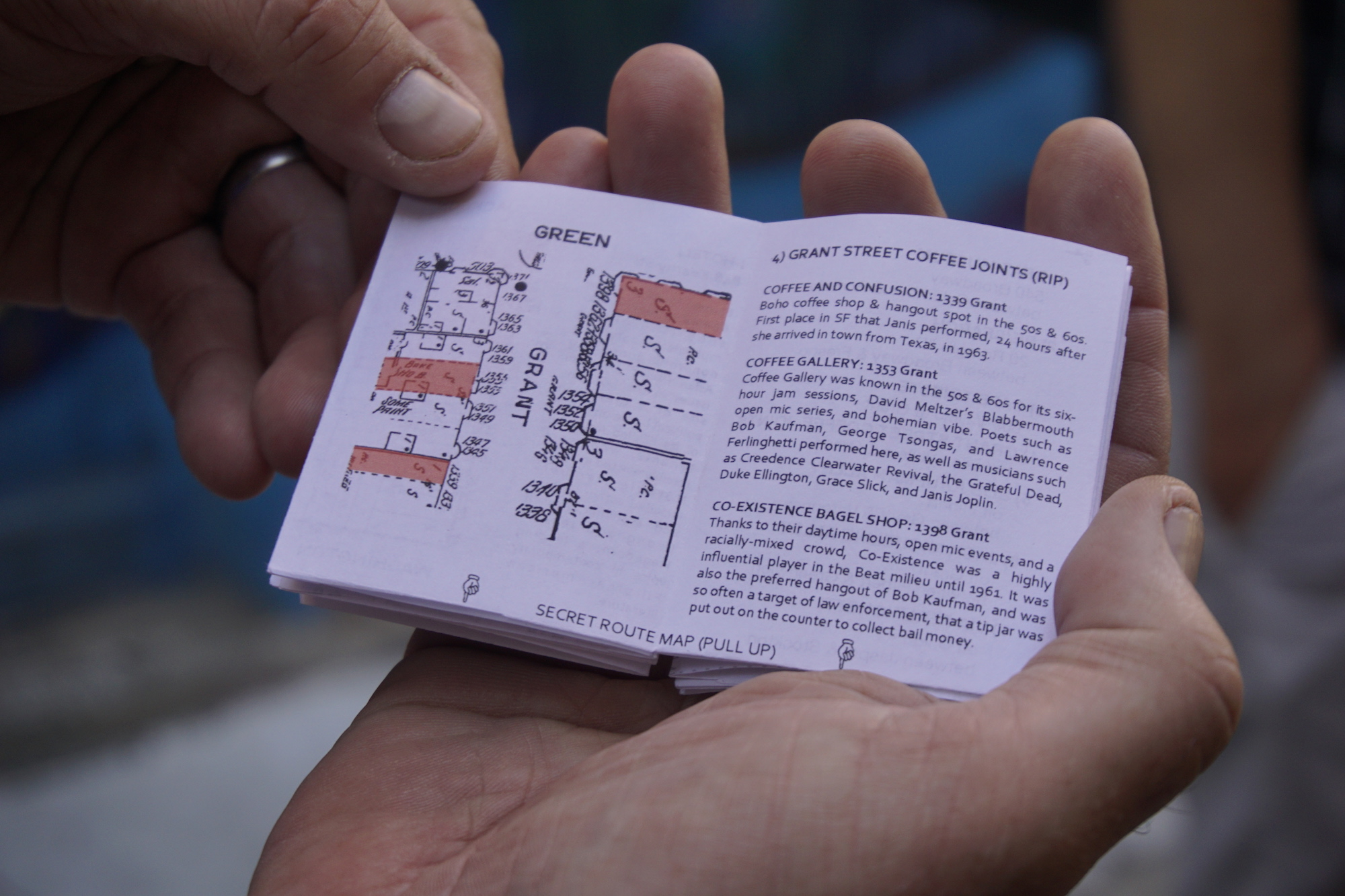 A pair of hands holding a small zine, opened to a page entitled Grant Street Coffee Joints (RIP)