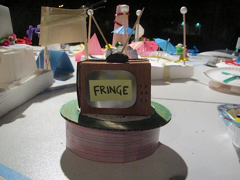 A craft table with a cardboard television on top of a ribbon reel with Fringe written on the front