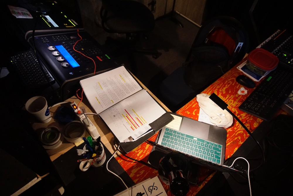 A low wooden shelf at right angles to a tech table, both covered with computers, lightboard, tech script, and coffee cups.
