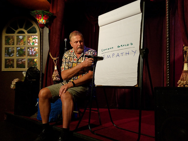 """Performer Ed Wolf, wearing a shirt patterned with Loteria game pieces and green shorts points a gun at a large sheet of paper on an easel, with the words """"common ground; empathy"""" written on it."""