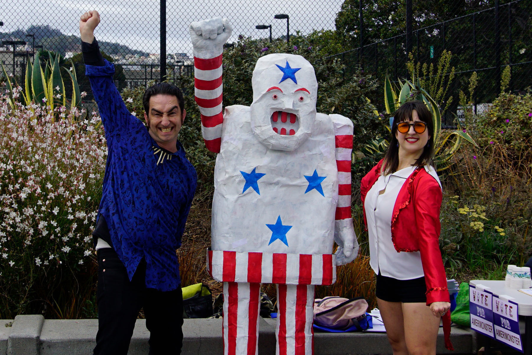 Two performers in red white and blue clothing pose next two a life-size golem puppet, the Amerimonster, with raised fists.