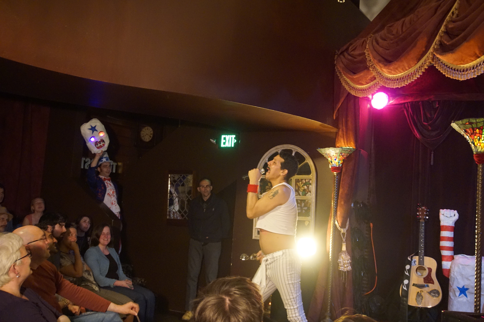Performer Peter Griggs dressed like Freddie Mercury in a white crop top, sings into a microphone in front of a smiling crowd.