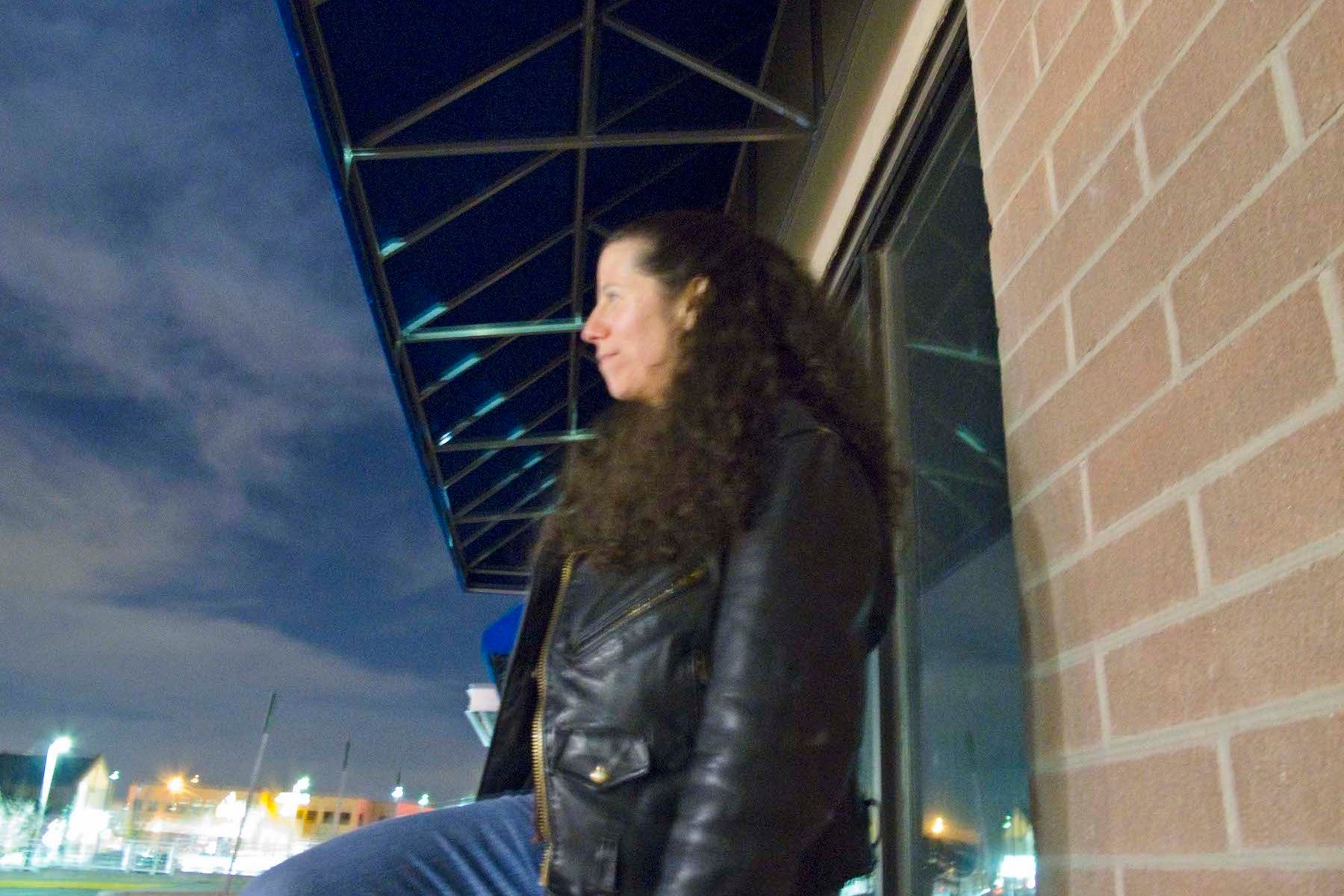 A woman with long curly dark hair, poses in a black leather jacket, gazing to the horizon.