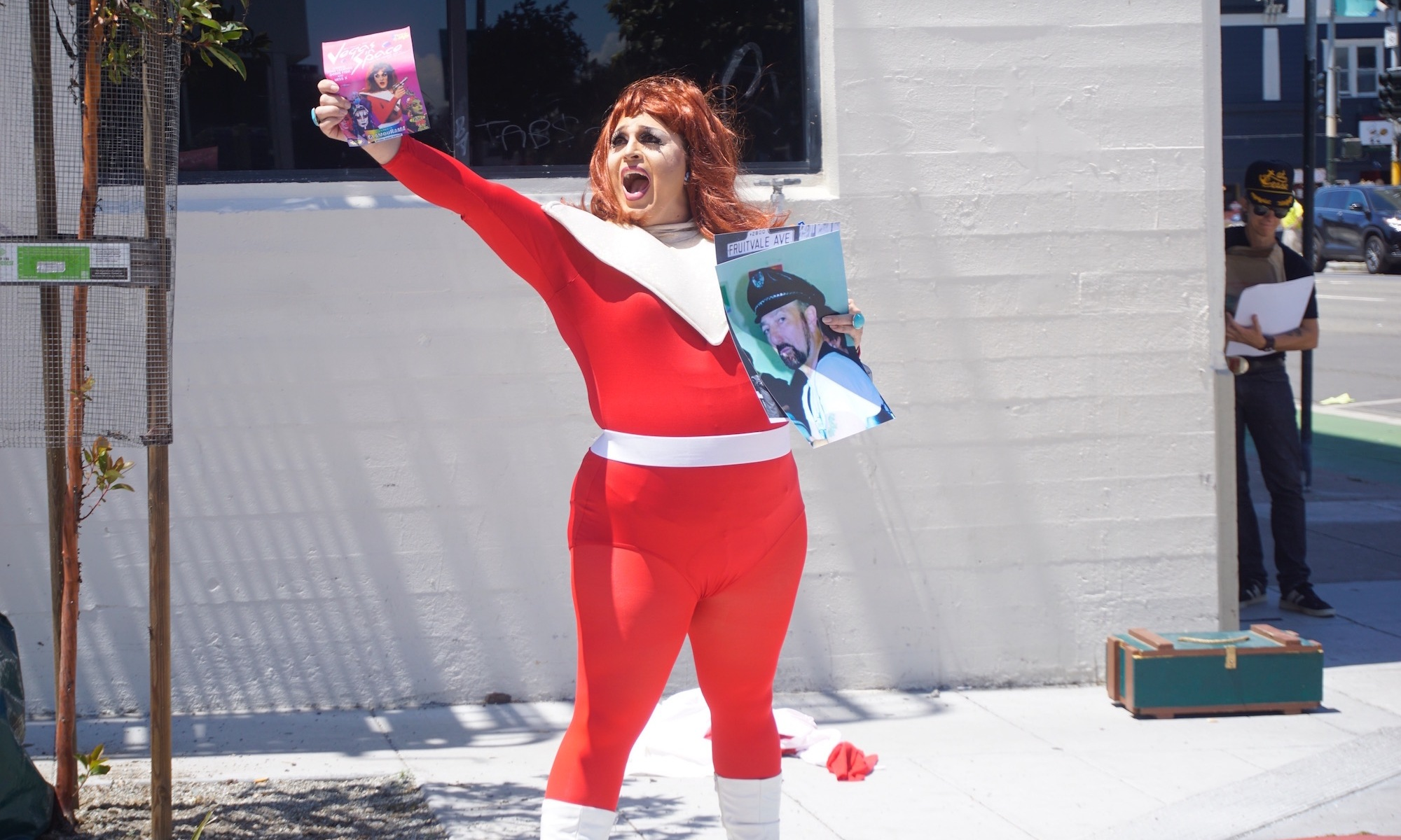 Performer Landa Lakes, a drag queen in a red and white spandex space suit, holds up flyers and photographs on a corner of Ringold Alley in San Francisco.
