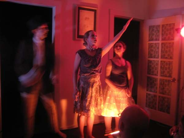 Three Dancers stand in a living room doorway, dim red lighting and artistically blurred image.
