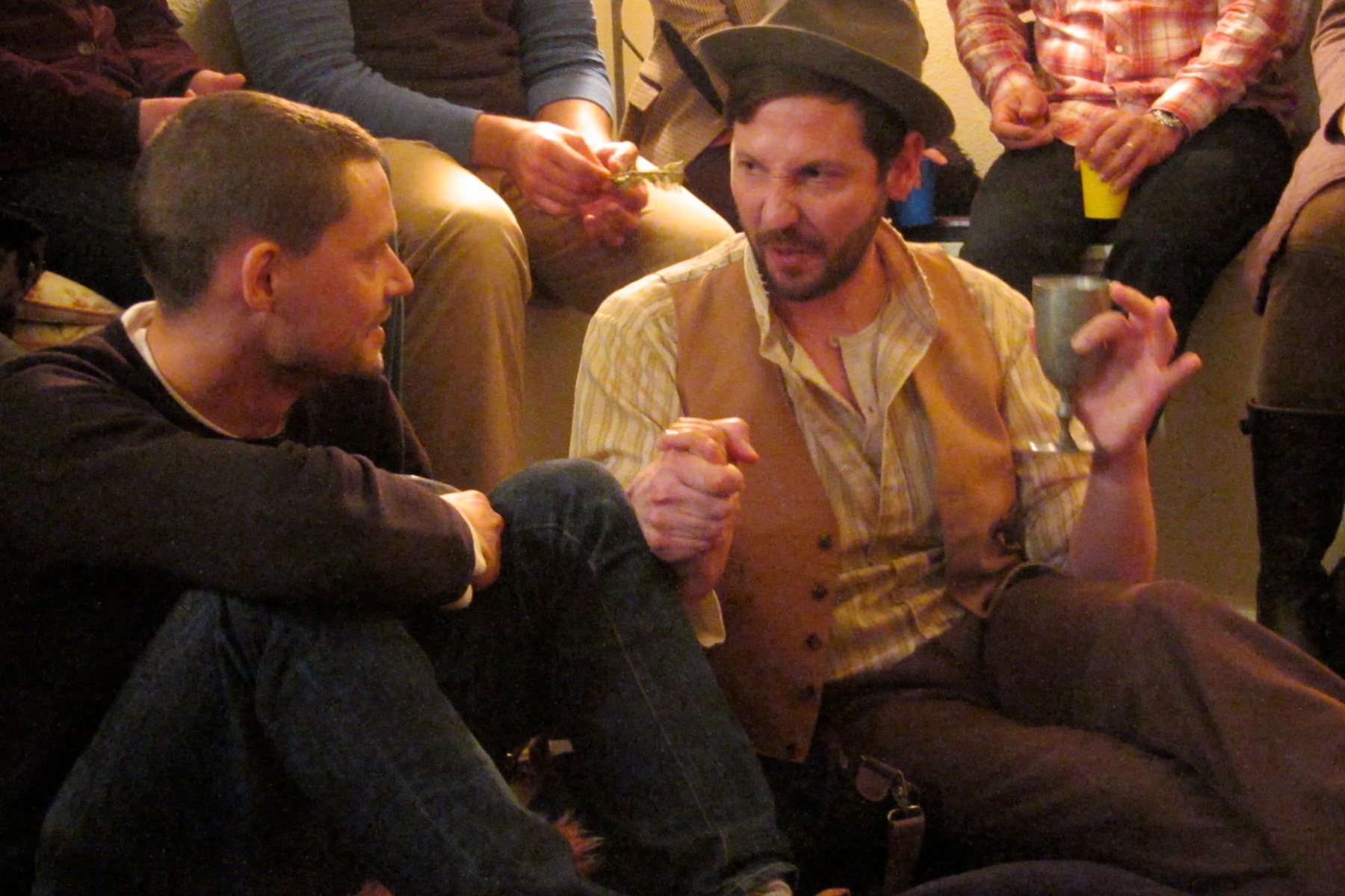 Performer Ryan Hayes in tan-colored vest, brown brimmed hat and yellow-striped shirt sits on the floor next to an audience member in a dark pullover top while holding a metal wine glass.