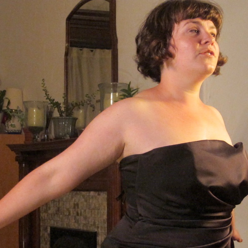 A performer in a black cocktail dress and short dark hair stands in a living room, arms outstretched behind her.
