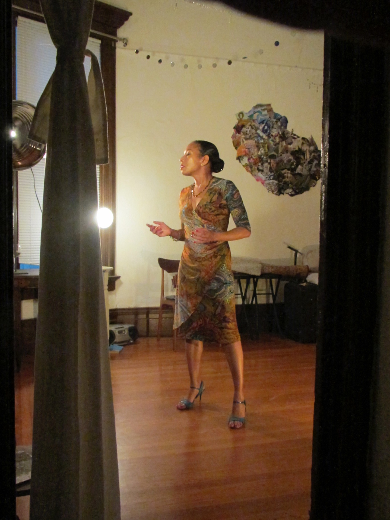 Performer Mia Paschal, a Black Woman with pulled back dark hair, stands in a living room on a wood floor in high heeled tango shoes and a wraparound dress of patterned grey and brown.