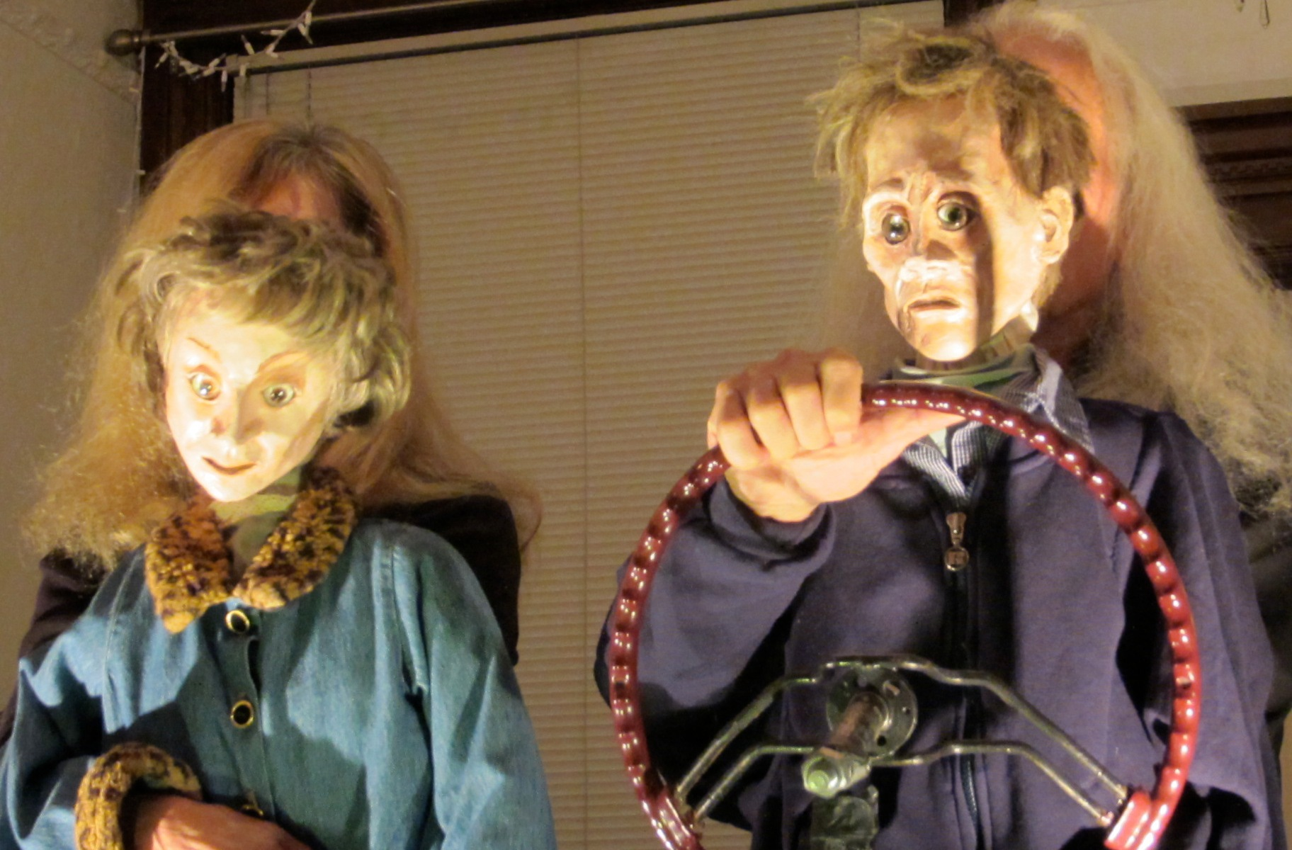 Two elderly performers wearing human-face masks pretend to drive a car in a private living room.