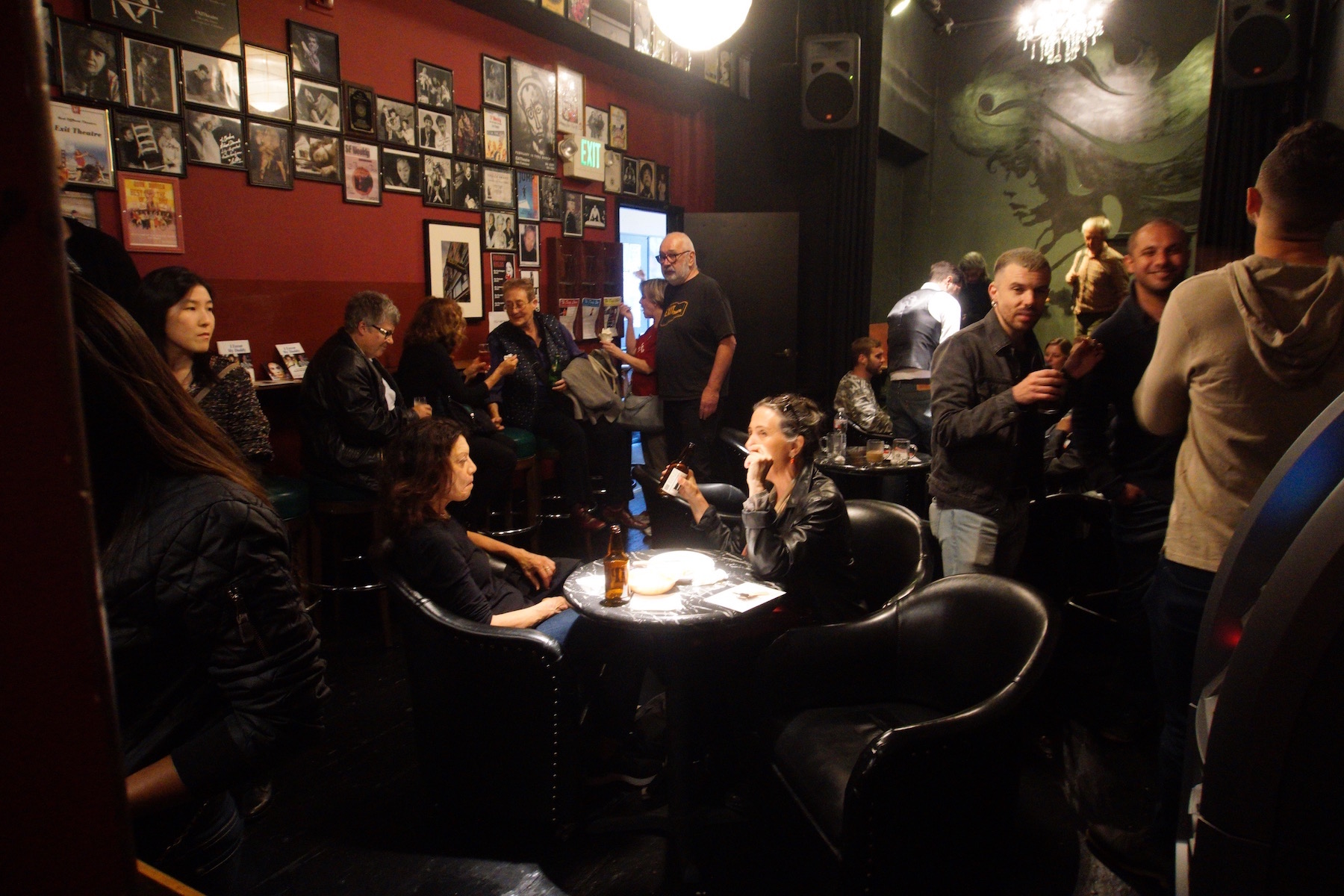 A crowd mingling in a dimly lit room with small round tables and large leather seats.