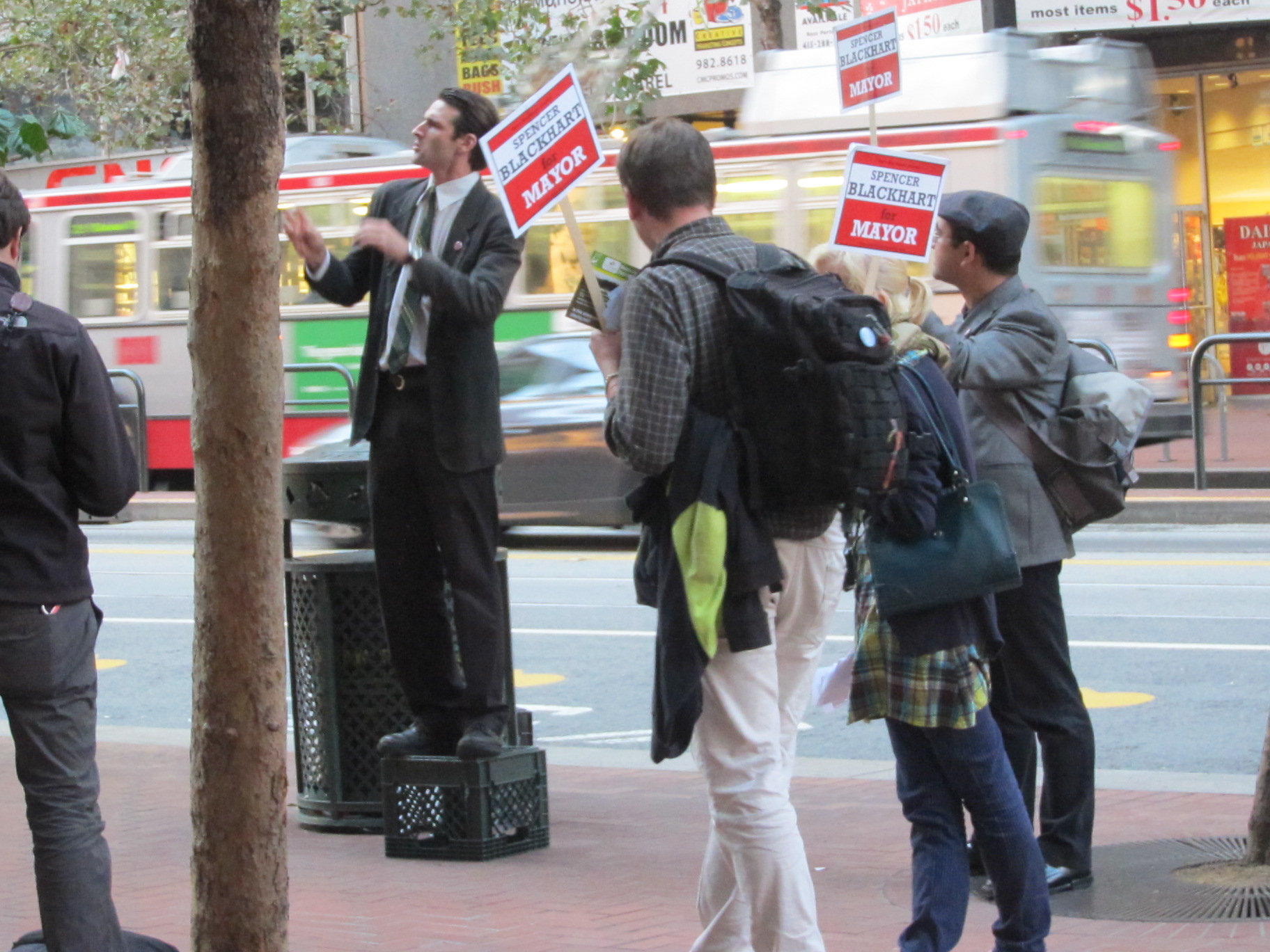 Spencer Blackhart performer in a dark suit and striped tie stands on a milk crate on a city sidewalk, as people carrying Spencer Blackhart for Mayor signs surround him.