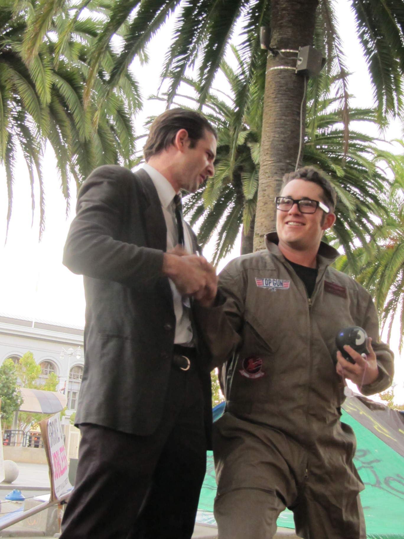 Spencer Blackhart performer in suit shakes the hand of a person wearing glasses and a Top Gun flightsuit.