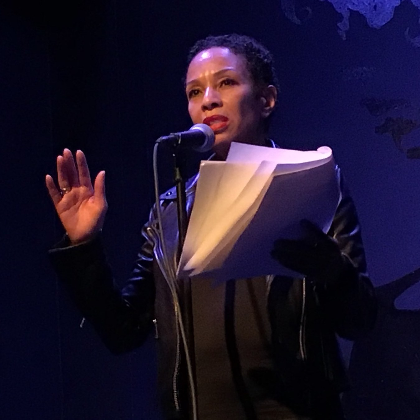 Performer Mia Paschal in a black leather jacket reads from a script onstage.