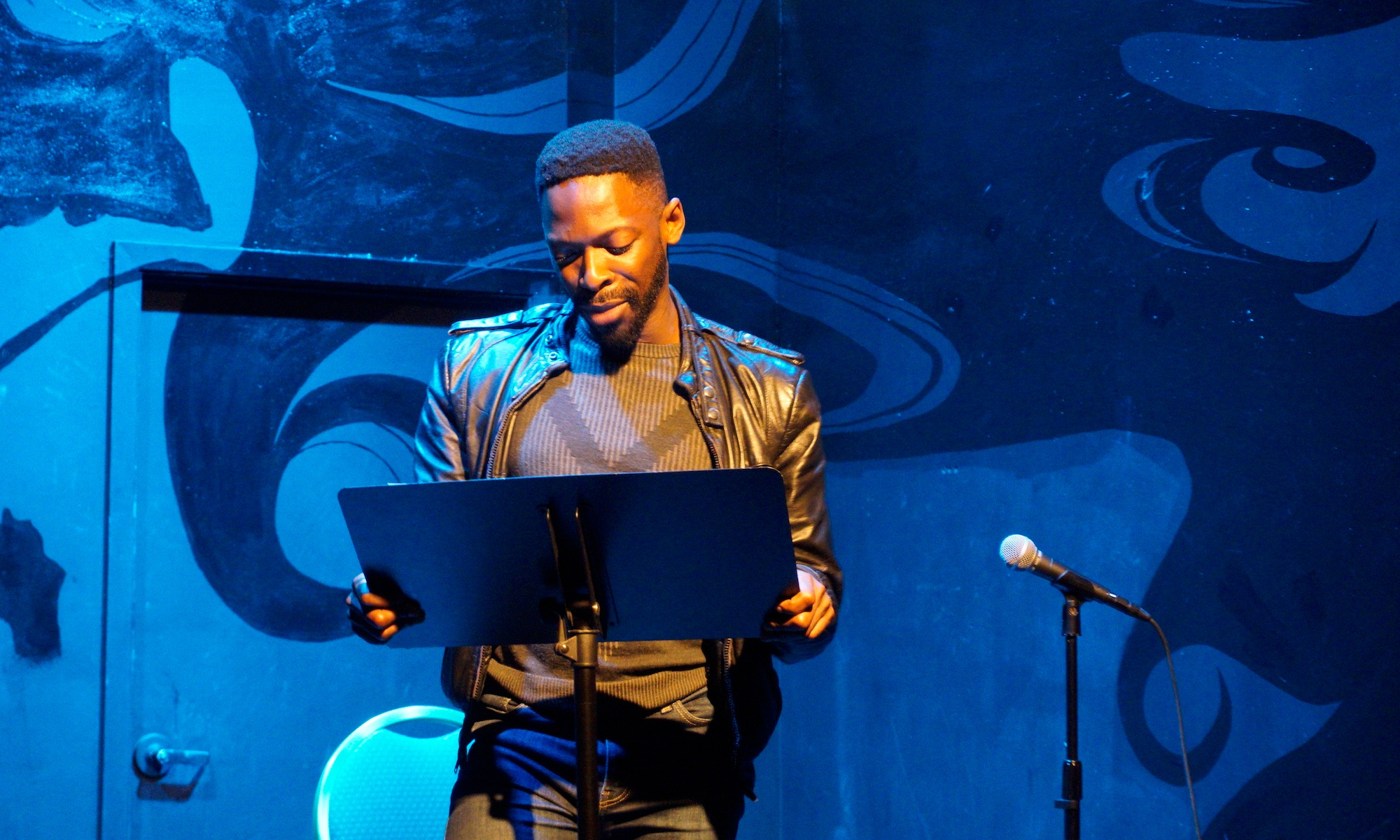 Performer Rotimi Agbabiaka in a black leather jacket and blue lighting stands behind a music stand onstage.
