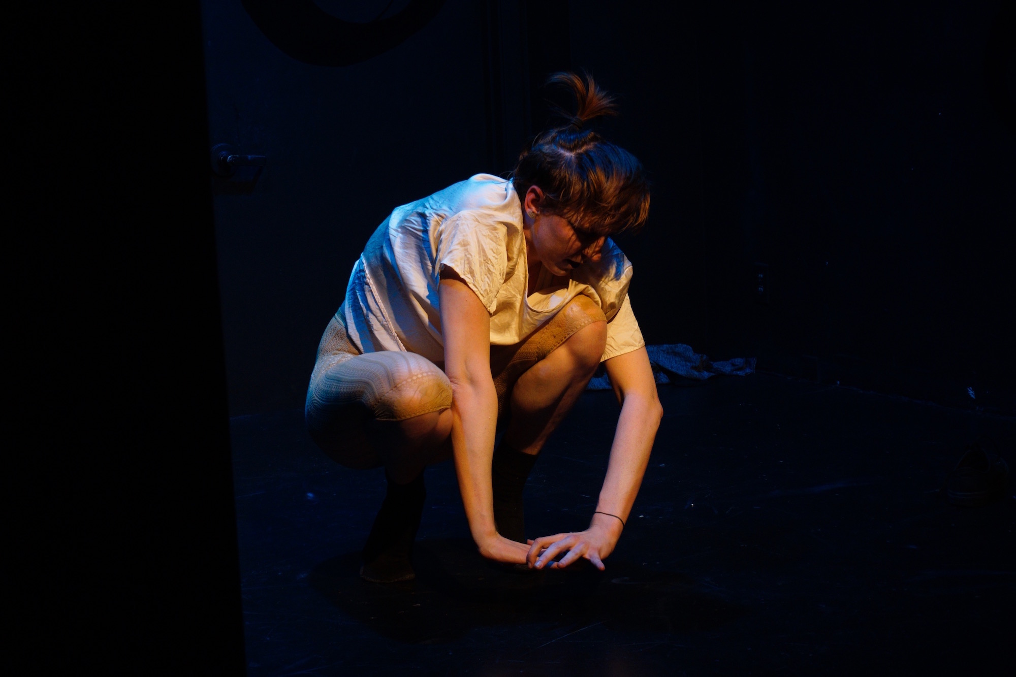 Fenner, a non-binary performer wearing a loose white shirt and tan leggings, crouches down onstage in a pool of light.