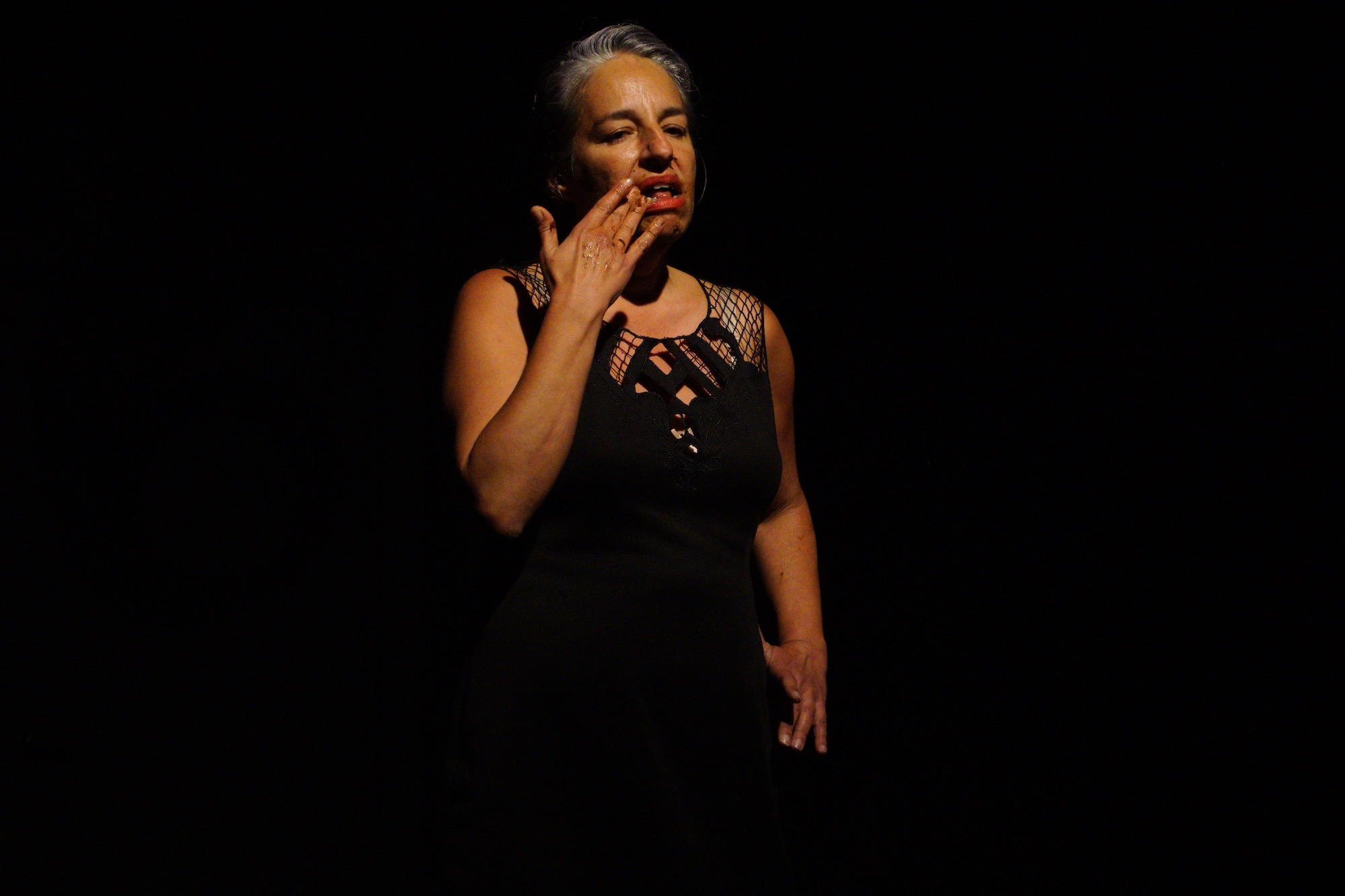 Performer Praba Pilar in a black dress and grey hair standing against a black background touching her mouth which is open and smeared.