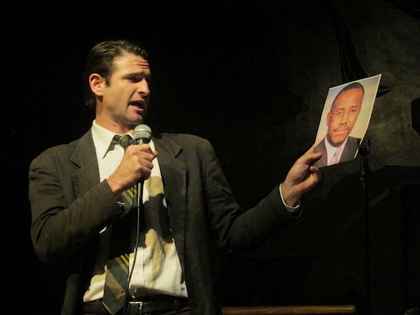 Performer Spencer Blackhart dressed in a dark suit and striped tie, holding a microphone and a photograph of a Black politician.