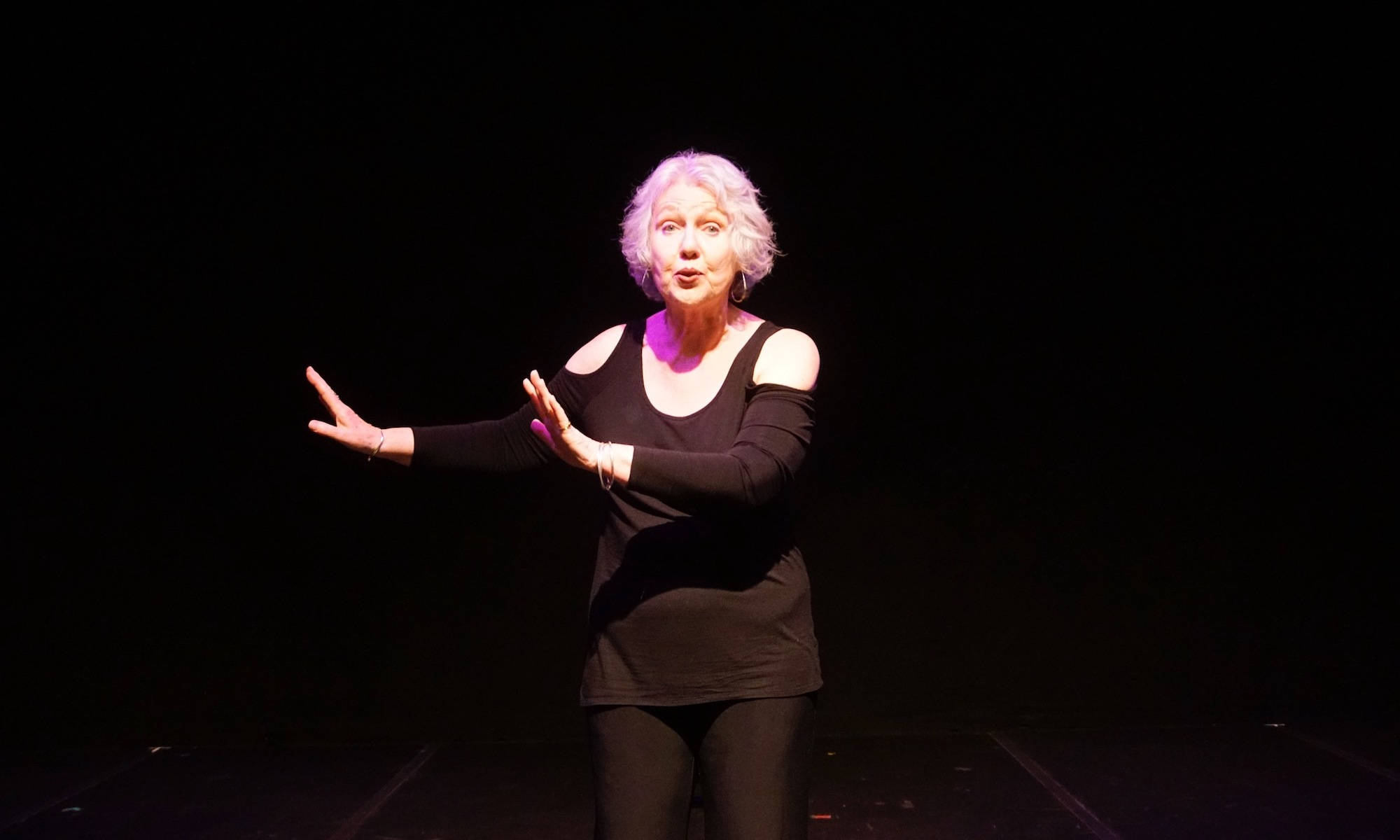 Christina Augello, Solo performer, white woman, senior citizen, stands onstage in black pantsuit, a lavender light on her face.